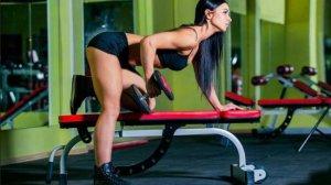 девушка в спортзале занимается с гантелями