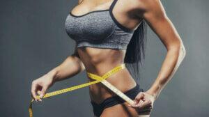 Девушка в фитнес форме измеряет свою талию