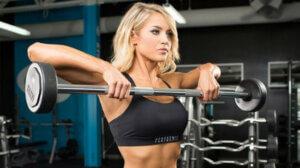 Девушка тренирует дельтовидные мышцы в зале